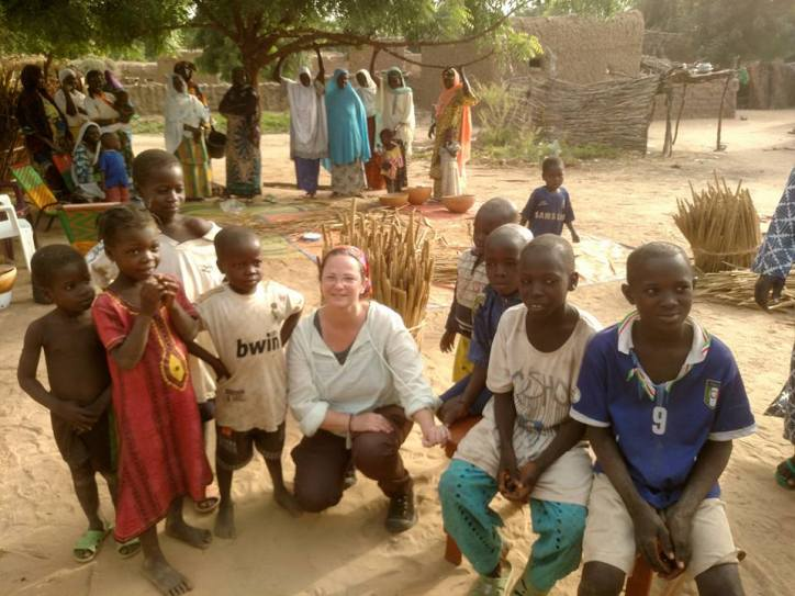 Susan posing for a photograph with several children.
